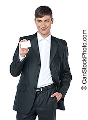 Young smiling business man handing a blank business card. Standing over white background