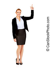 Young smiling business woman pointing up