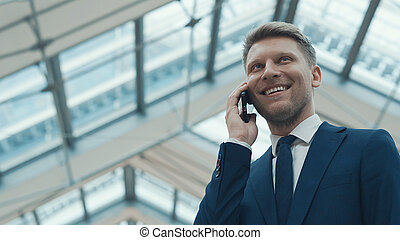 Young smiling businessman talking on the phone