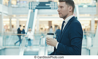 Young smiling businessman with coffee