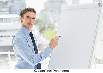 Young smiling businessman writing on whiteboard with marker