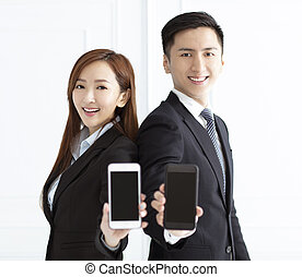 Young smiling businesswoman and businessman showing smart phone