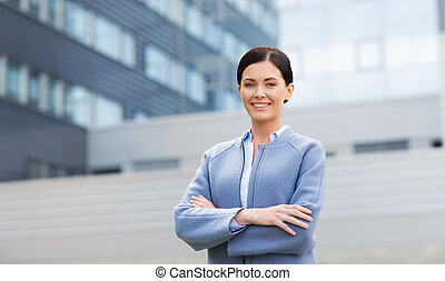 young smiling businesswoman over office building