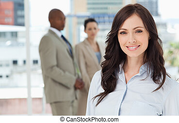 Young smiling businesswoman standing in front of her colleagues