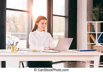 young smiling caucasian businesswoman working on laptop in office