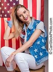 young smiling caucasian woman posing in front of USA flag, Independence Day of America