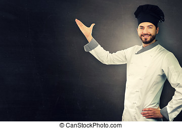 young smiling chef in white uniform on black with copy space
