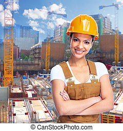 Young smiling Construction worker girl. Architecture background.