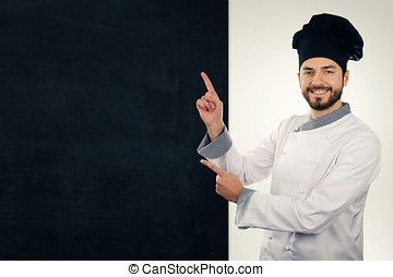 young smiling cook pointing on blank blackboard. copy space