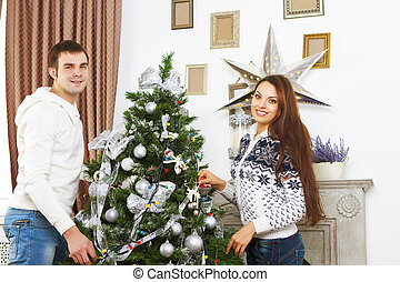 Young smiling couple by the Christmas tree