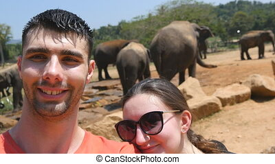 Young smiling couple doing selfie photo with elephants in surroundings of reserve in Sri Lanka