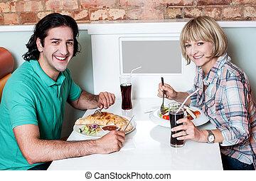 Young smiling couple enjoying lunch