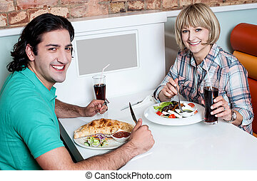 Young smiling couple enjoying meals