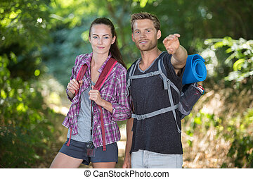 young smiling couple hiking in forest