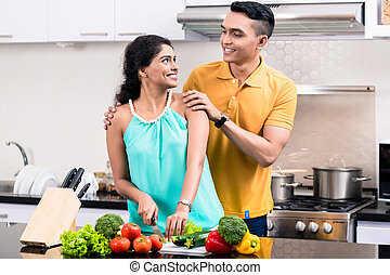 Young smiling couple in the kitchen looking at each other