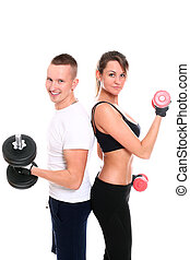 Young smiling couple lifting dumbbells in studio