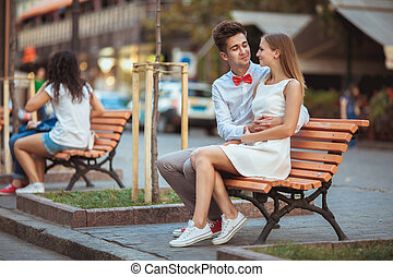 Young smiling couple looking on each other - sitting on bench