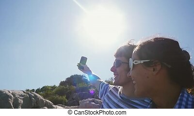 Young smiling couple wearing sunglasses taking selfie portrait by beautiful mountain with lense flare effects on the sun on the background in slow motion.