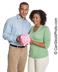 Young smiling couple with a pink piggy bank isolated against white background