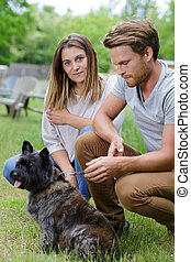 young smiling couple with small dog relaxing on nature