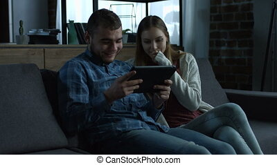 Young smiling couple with tablet relaxing on sofa
