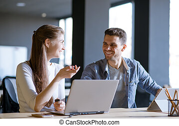 Young Smiling Coworkers Woman and Man Discusing Working Details and Pointing at Laptop Screen in Office
