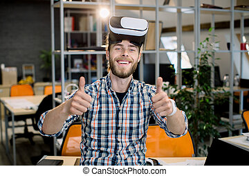 Young smiling creative handsome bearded man working in the office, trying a new product or playing game with virtual reality goggles, posing to camera showing his thumbs up