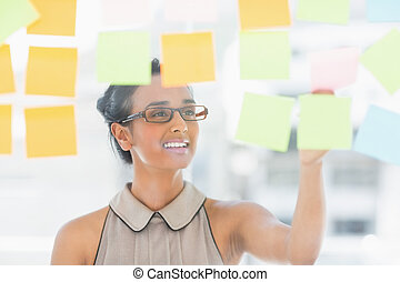 Young smiling designer looking at sticky notes on window