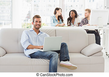 Young smiling designer working on his laptop on the couch in...