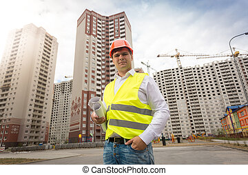 Young smiling engineer standing on building site