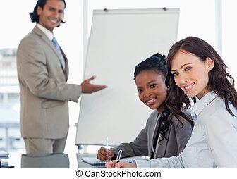 Young smiling executives sitting at the desk with a co-...