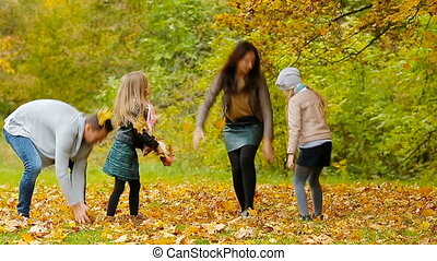 Young smiling family throwing leaves around on an autumn day outdoors