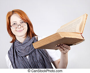 Young smiling fashion girl in glasses with old book
