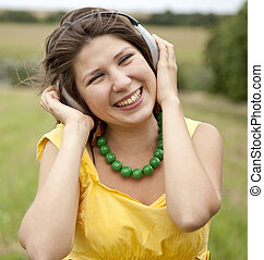 Young smiling fashion girl with headphones at field.