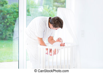 Young smiling father putting his newborn baby in a white round c