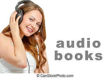 Young smiling female listens to audio book over headphones. ...