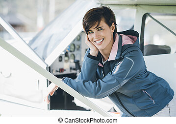 Young smiling female pilot leaning on a plane