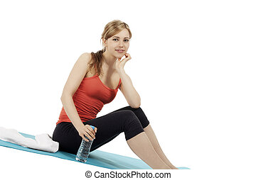 young smiling fitness woman sitting with a bottle of water on white background