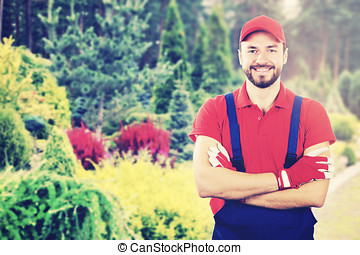 young smiling gardener with crossed arms standing in garden