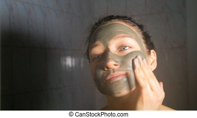 Young smiling girl applying a cosmetic mask of blue clay in the bathroom, 4K.
