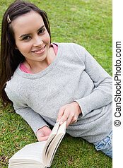 Young smiling girl looking at the camera while holding a book