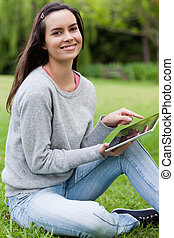 Young smiling girl looking straight at the camera while using her tablet computer