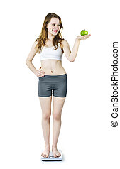 Young smiling girl on bathroom scale holding apple