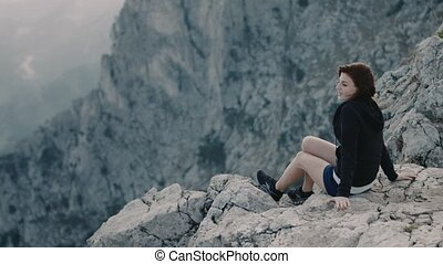 Young smiling girl sits on the edge of mountain