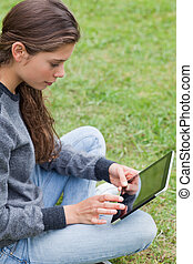 Young smiling girl sitting cross-legged on the grass while touching her tablet pc
