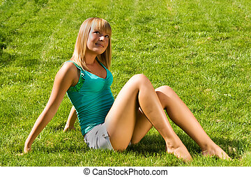 Young smiling girl sitting on grass