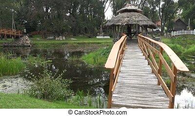 young smiling girl walk on vintage wooden bridge over stream. 4K