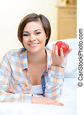 Young smiling girl with an apple.