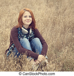 Young smiling girl with headphones at field.