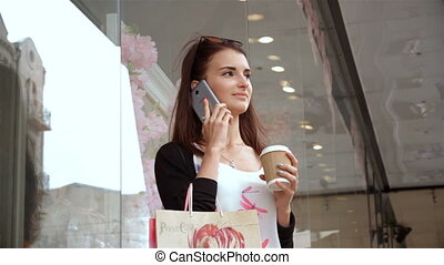 young smiling glamour Lady with purchases worth on the street drinking coffee and talking on the phone